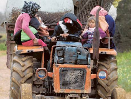 Fleeing Syrian farmers with their children in a tractor arrive in Al Qaa village in northern Lebanon