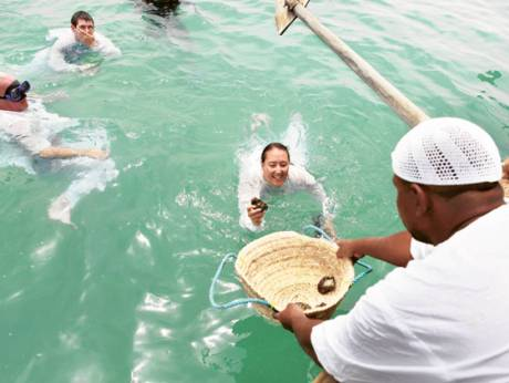 Tourists receive a pearl diving demonstration from trained professionals