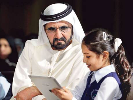 Shaikh Mohammad watches a pupil use a tablet
