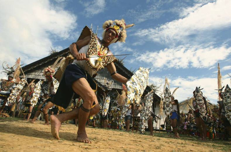 a-tribesman-from-dayak-kenyah-wearing-a-traditional-costume-performs-a-war-dance