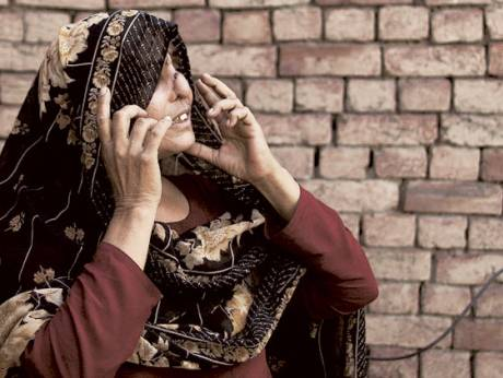 Allah Rakhi, whose nose was sliced by her husband, adjusts her scarf at her home