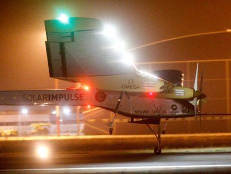 An experimental solar-powered plane, Solar Impulse, approaches to make a night landing