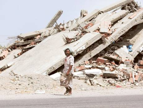 A man walks past a building destroyed during fighting with Al Qaida militants in the town of Jaar