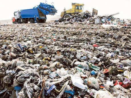 A compactor handles trash at the Al Saj'ah landfill in Sharjah