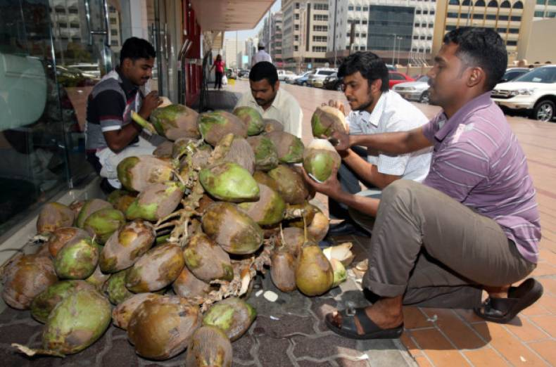 a-fruits-vegetable-shop-vendor-selling-tender-coconuts-to-the-customers