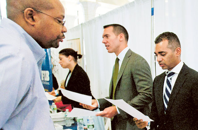 job seeker speaks with an employer at the Veterans On Wall Street job fair in New York