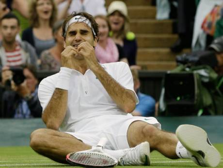 Roger Federer  celebrates with the trophy after winning Wimbledon