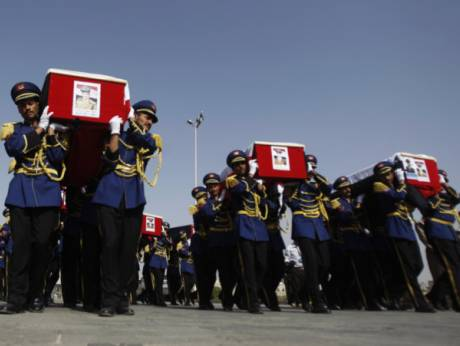 Honour guards carry the coffins of nine police academy cadets