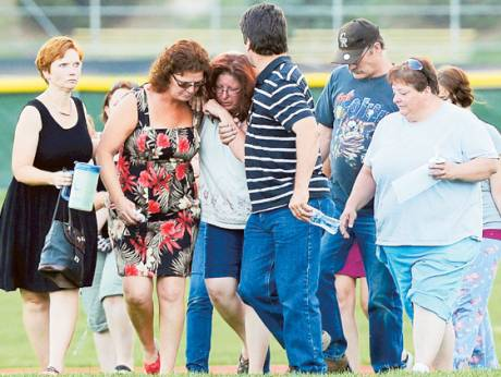 Colorado theatre shooting victim A.J. Boik's mother (centre) is helped off the football field