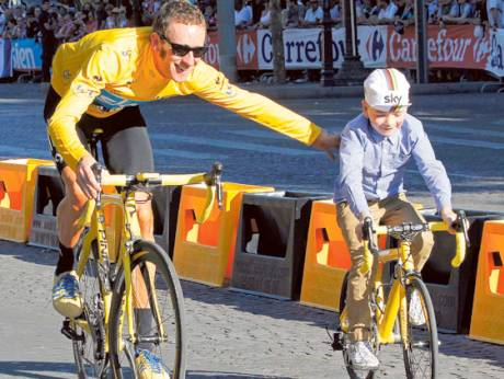 Sky Procycling rider and leader's yellow jersey Bradley Wiggins of Britain rides with his son Ben
