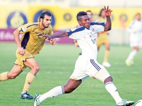 Yousuf Mohammad of Dubai and Asamoah Gyan of Al Ain in action