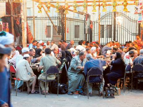 Muslims eat an iftar meal provided by volunteers for the needy in Cairo