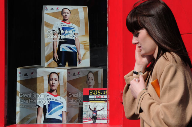 a woman walks past a adverts featuring British athlete Jessica Ennis in a shop window in London