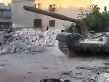A Syrian military tank rolls through a street in Aleppo