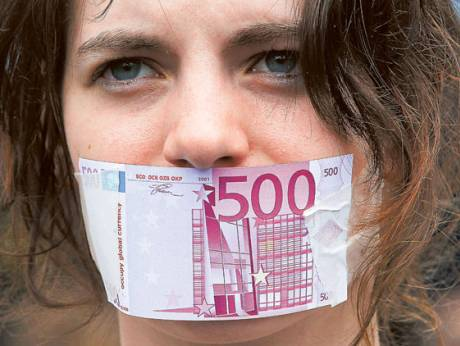 A protester tapes a replica of a €500 bill over her mouth during an anti-capitalism demonstration