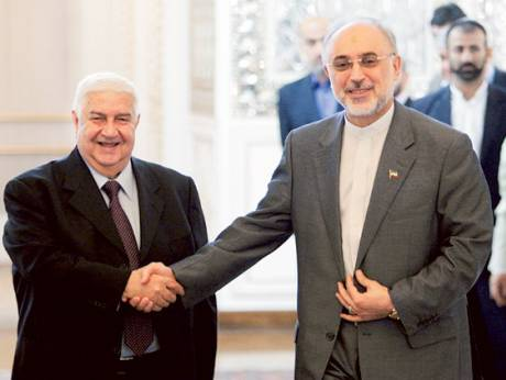 Ali Akbar Salehi, right, shakes hands with his Syrian counterpart Walid Mua'alem