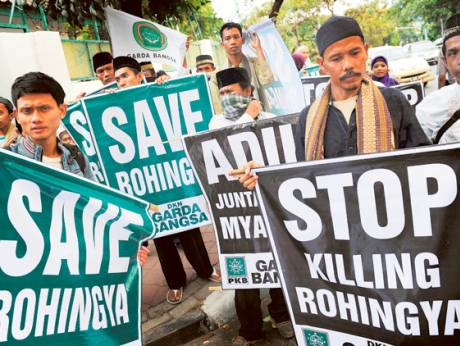 Indonesian Muslims hold placards supporting the Rohingya