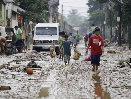 Filipinos walk along a muddy road in Marikina