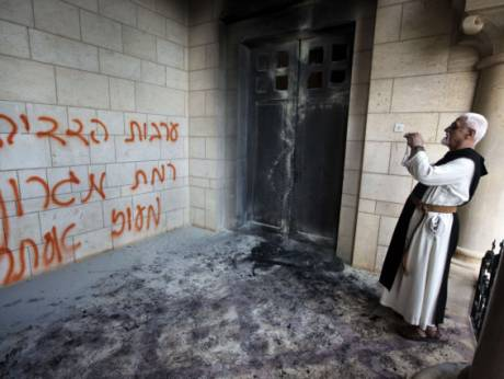 A priest stands near a burnt door of a monastery
