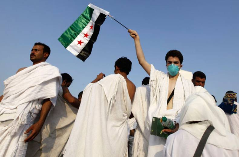a-syrian-pilgrim-waves-a-flag-on-mount-mercy-on-the-plains-of-mount-arafat