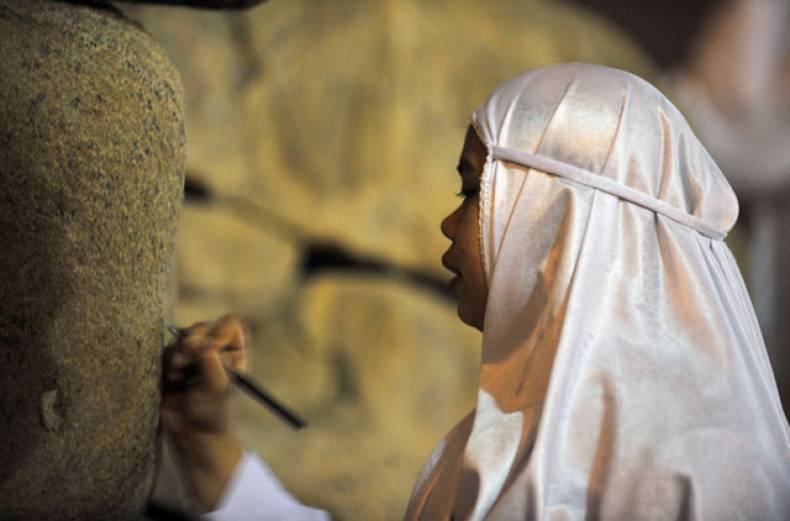 a-pilgrim-writes-her-name-on-the-rocks-at-mount-arafat