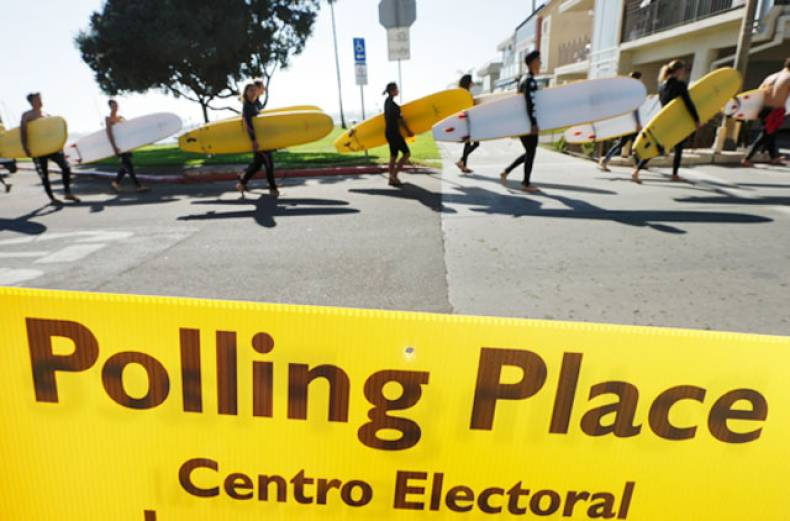 a-surfing-class-passes-a-sign-for-a-polling-place-as-voters-head-to-the-polls-tuesday-in-san-diego