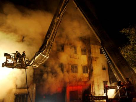 Bangladeshis and firefighters battle a fire at a garment factory