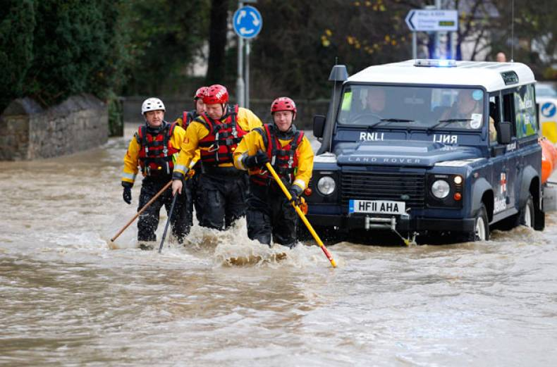 a-royal-national-lifeboat-institution-rnli-crew-make-their-way-through-flood-waters-in-st-asaph