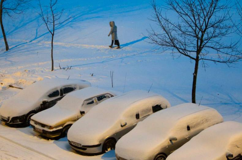 a-woman-walks-behind-a-row-of-cars-after-snow-fall