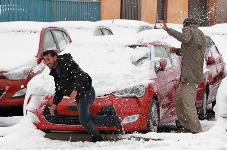 men-play-in-the-snow-after-a-heavy-snowstorm-in-amman
