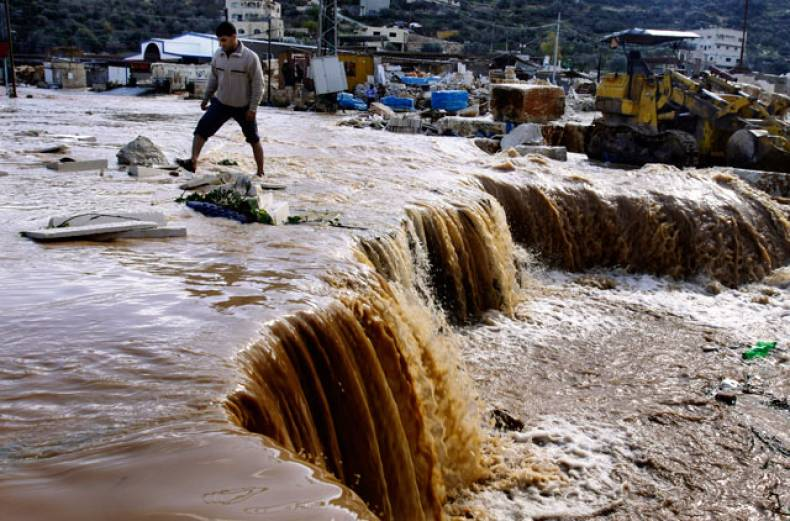 palestinians-cross-a-road-flooded-and-swept-away-by-heavy-rains-in-the-northern-west-bank-village