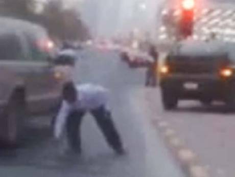A resident scrambles for money blown through the streets of Kuwait