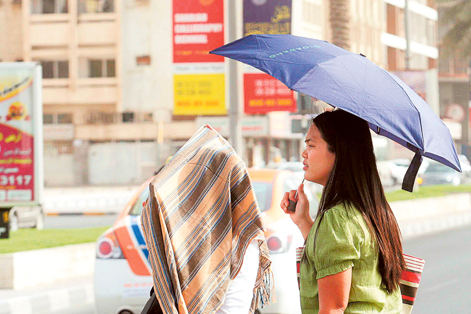 People use umbrella to protect themselves from the sun's rays in Sharjah