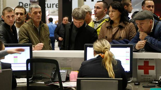 People gather at the airline information desk in Russia