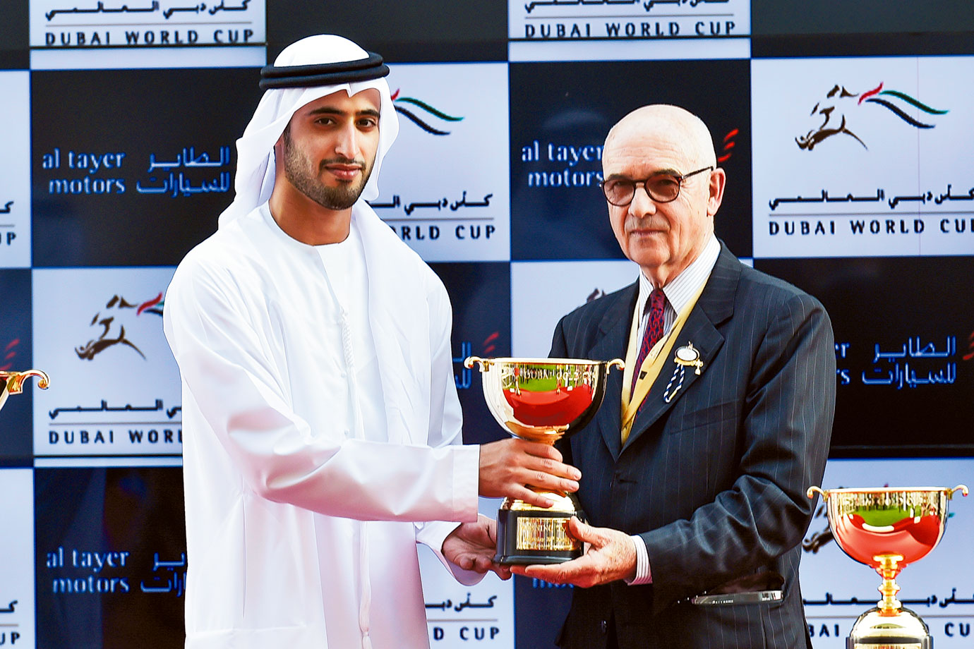 Humaid Tariq Al Tayer presents the trophy to the trainer Alain De Royer-Dupre