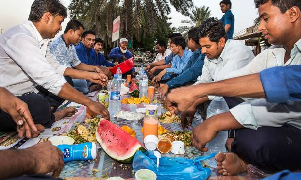a group of vegetable sellers end their fast at Al Aweer fruits and vegetable market