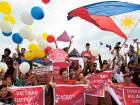 Filipino activists and Vietnamese nationals release balloons and wave Philippine flags.