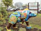 A life-size, fiberglass bear statue painted with nature scenes and rubber boots, part of a 'Parade of Bears' display, stands in front of offices of Great Land Trust.