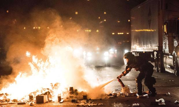 A police officer attempts to extinguish a fire on the I-85 (Interstate 85) during protests