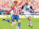 Atletico Madrid's forward Antoine Griezmann (left) kicks the ball beside Deportivo La Coruna's midfielder Guilherme during their match on Sunday.