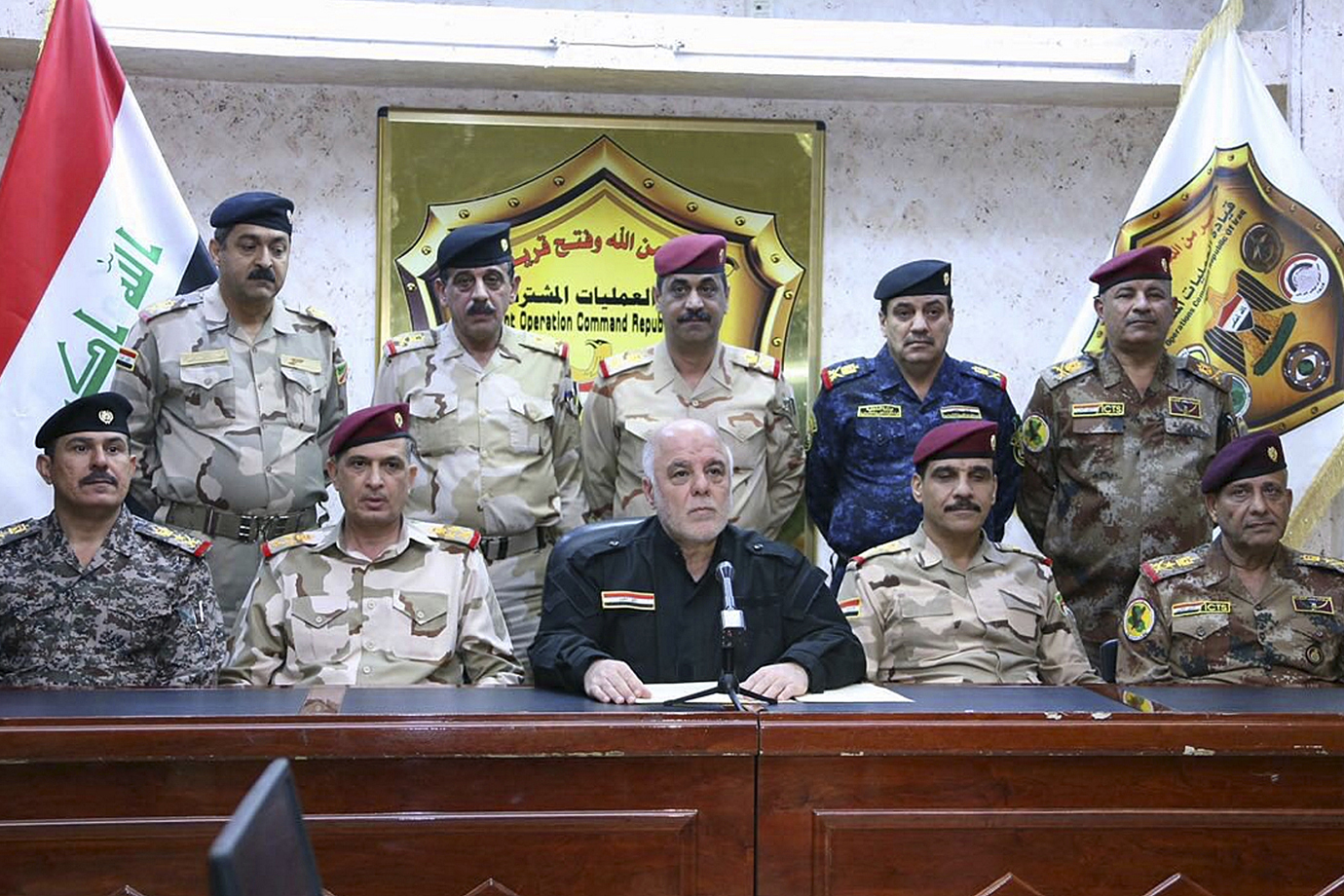 Iraqi Prime Minister Haider Al Abadi, centre, surrounded by top military and police officers as he a