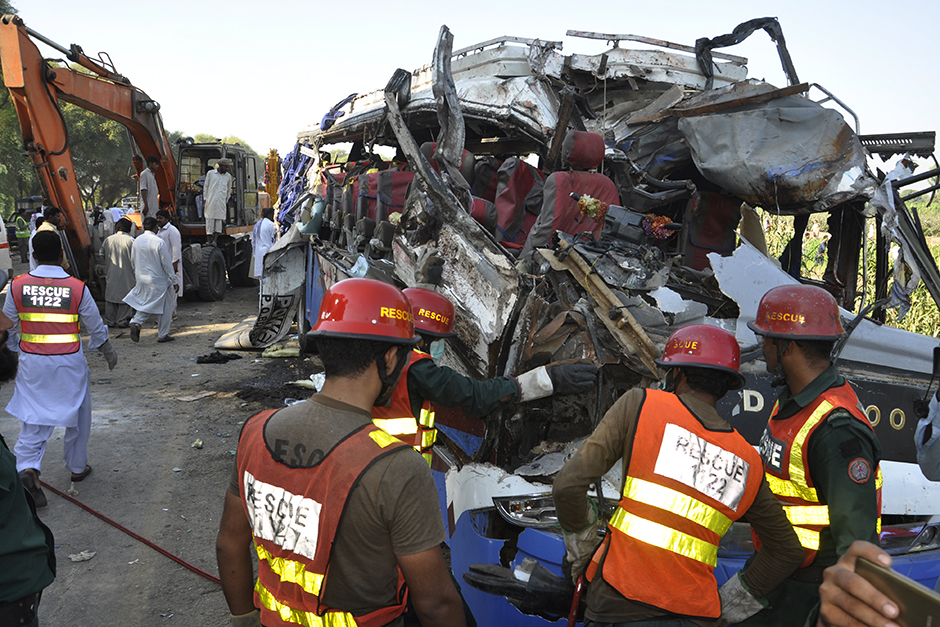 A rescue team work on the wreckage of a deadly accident involving two buses, in Khanpur