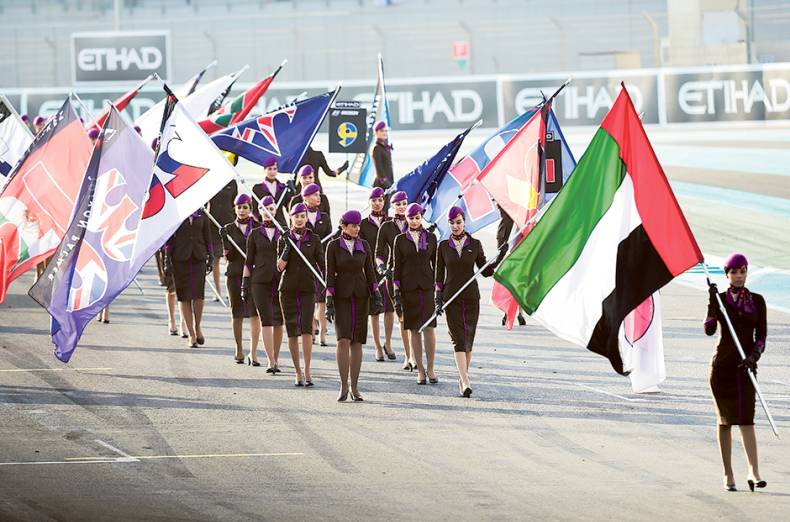 etihad-grid-girls-walk-the-track-with-flags-before-the-start-of-the-race