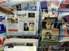 In this Tuesday, April 5, 2011, file photo, a man picks up a copy of Al Wasat newspaper at a newsstand in Hamad Town, Bahrain.