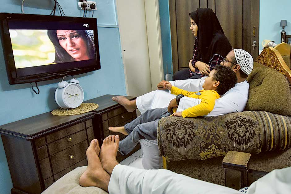 A family watching TV in Sharjah at their residence.