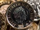 New British one pound coins on display on the production line at the Royal Mint in Llantrisant, U.K., on Thursday, March 23, 2017.
