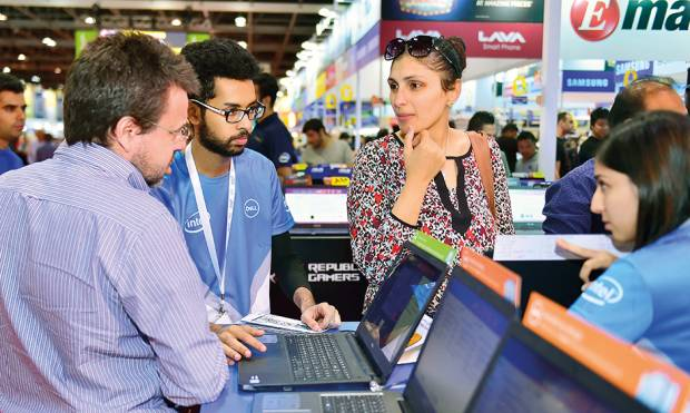 Customers check out laptops on display at Gitex Shopper.