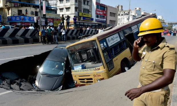 Bus, car plunge into crater as road caves in