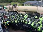 Protesters and police stand by as trailers carrying US THAAD missile defence equipment enter a deployment site in Seongju, early on April 26, 2017. Arrival of the six trailers at the golf course location sparked clashes between locals and police, the agency said.