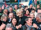 French presidential election candidate Marine Le Pen (centre) smiles with workers in front of the Whirlpool factory in Amiens, northern France, on Wednesday.